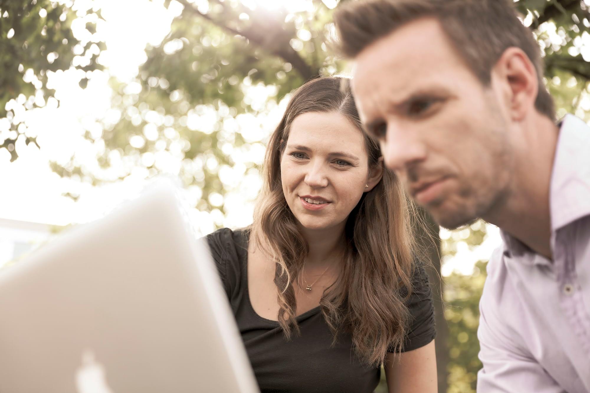 Eine Frau und ein Mann schauen auf den Bildschirm eines Laptops
